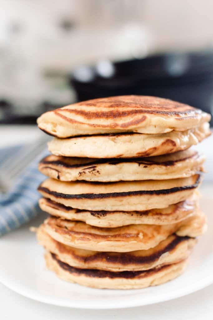 large stack of fluffy einkorn pancakes on a white plate