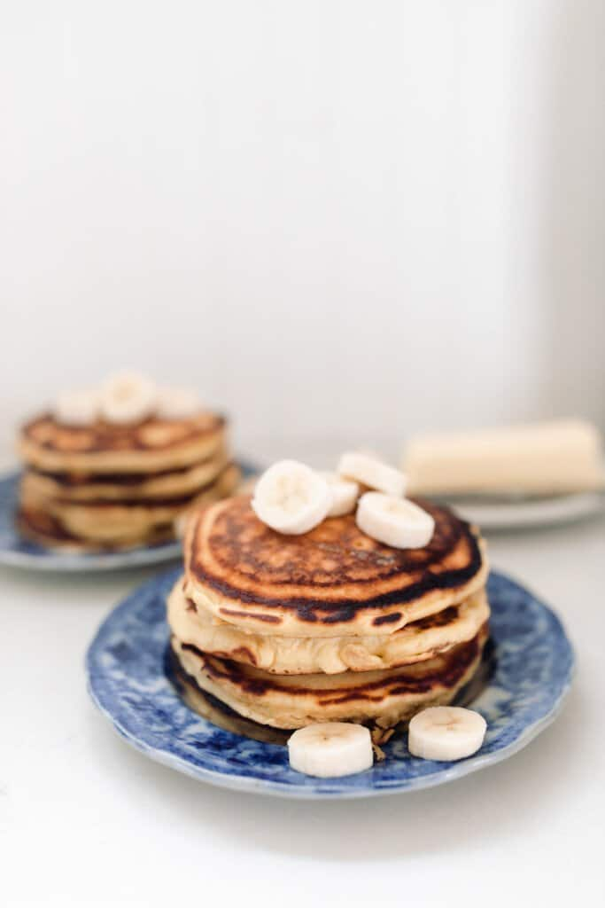 two stacks of pancakes with bananas on blue plates on a white countertop