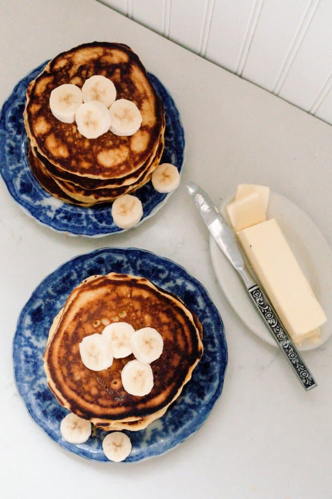 overhead photo of einkorn pancakes topped with bananas on a blue and white antique plates. a dish with butter and a knife sit to the right of the pancakes