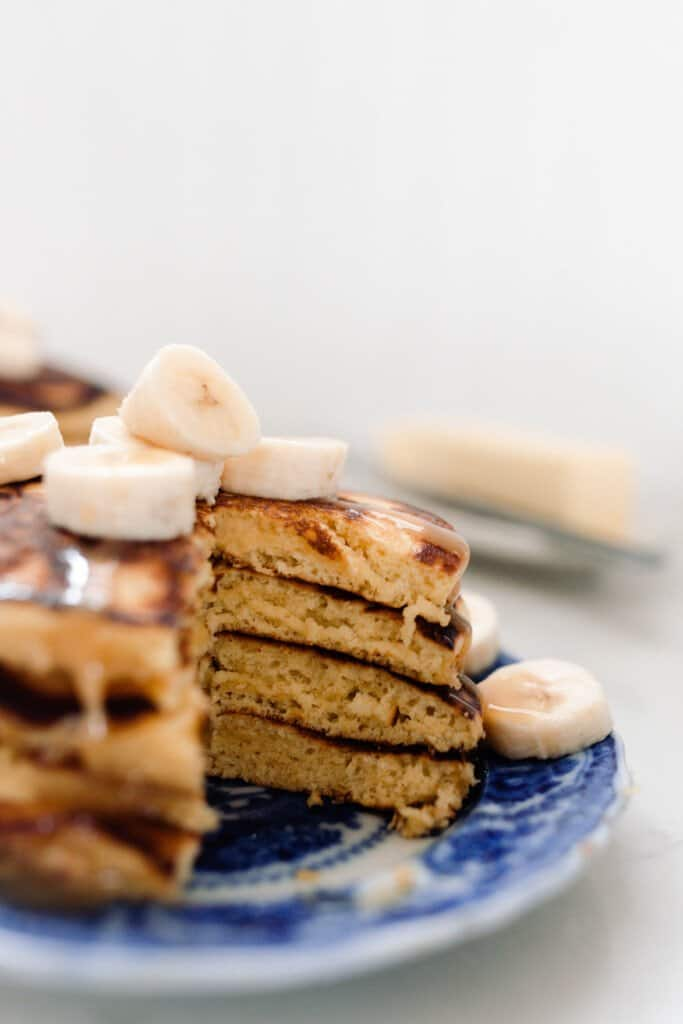 pancakes stacked four high and topped with bananas