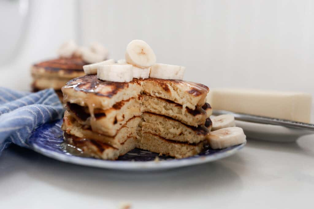 two stacks of einkorn pancakes with bananas on a white and blue antique plate on a white countertop