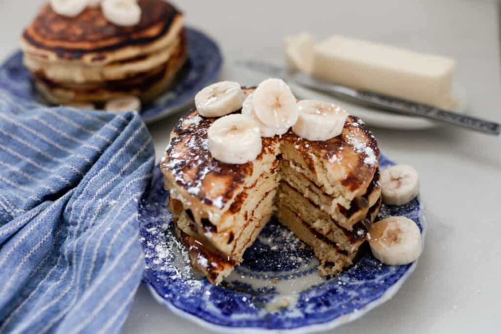 a stack of fluffy einkorn pancakes topped with syrup and sliced banana on a antique blue and white plate with another stack in the background