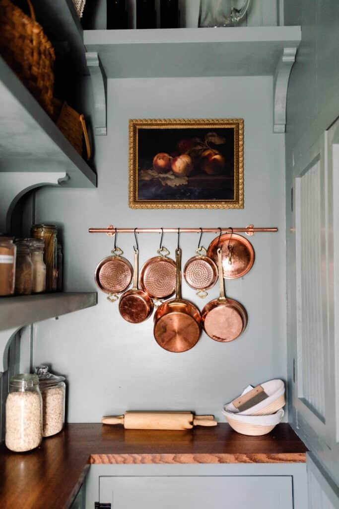 victorian farmhouse pantry with blue green walls, cabinets with wood countertops, shelving, and copper pots handing on the wall