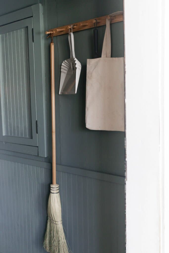 peg rail against a blue green wall with a handmade broom, white dustpan and canvas tote hanging on the pegs