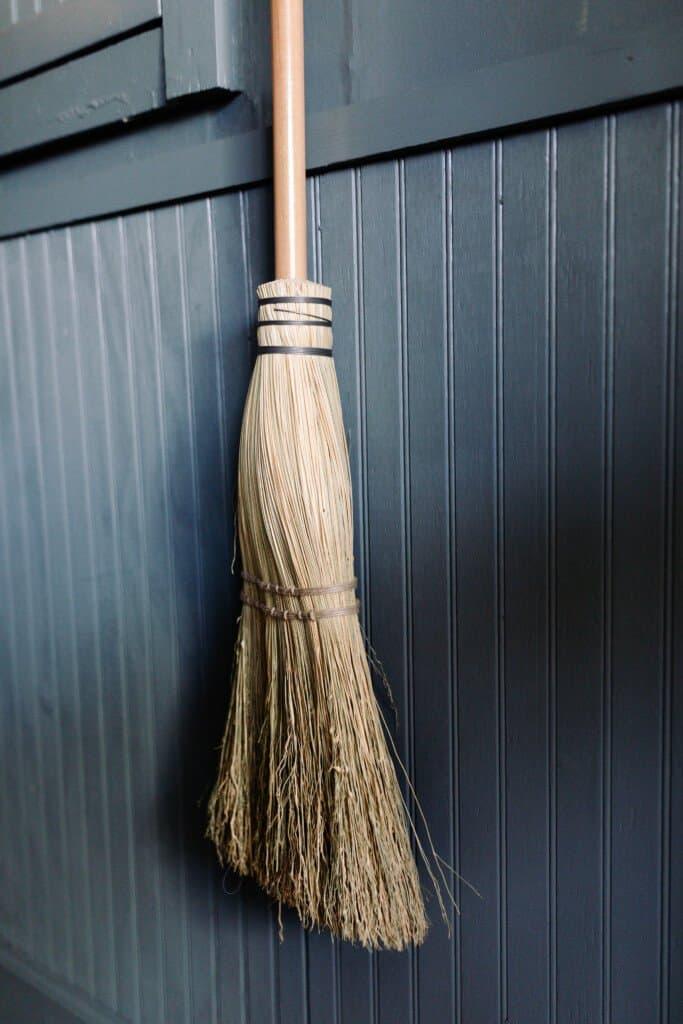 handmade wooden broom against a blue green