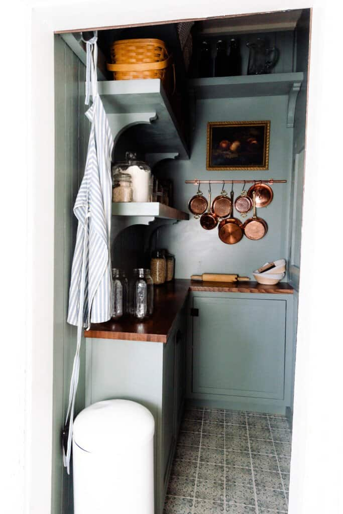 farmhouse pantry reveal with custom blue/green cabinetry, shelving, peach art in a vintage frame, and copper pots hanging on the wall.