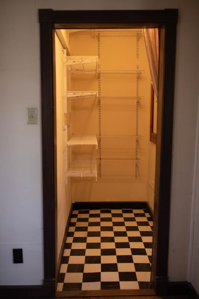 Pantry before with black and white tile and wire shelving