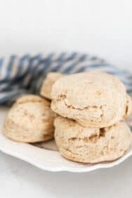 sourdough biscuits stacked on a white plate with a blue and white stripped towel in the background