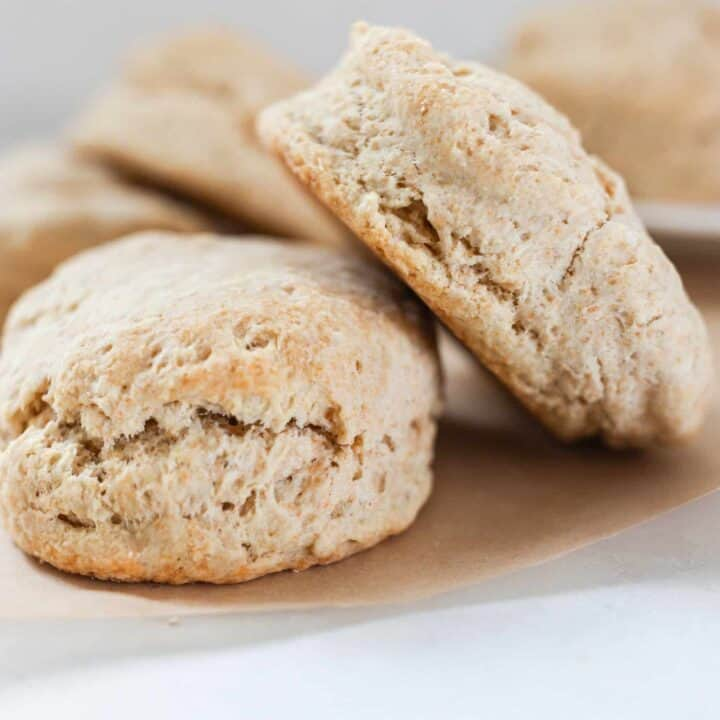 golden sourdough biscuits stacked on a piece of parchment paper