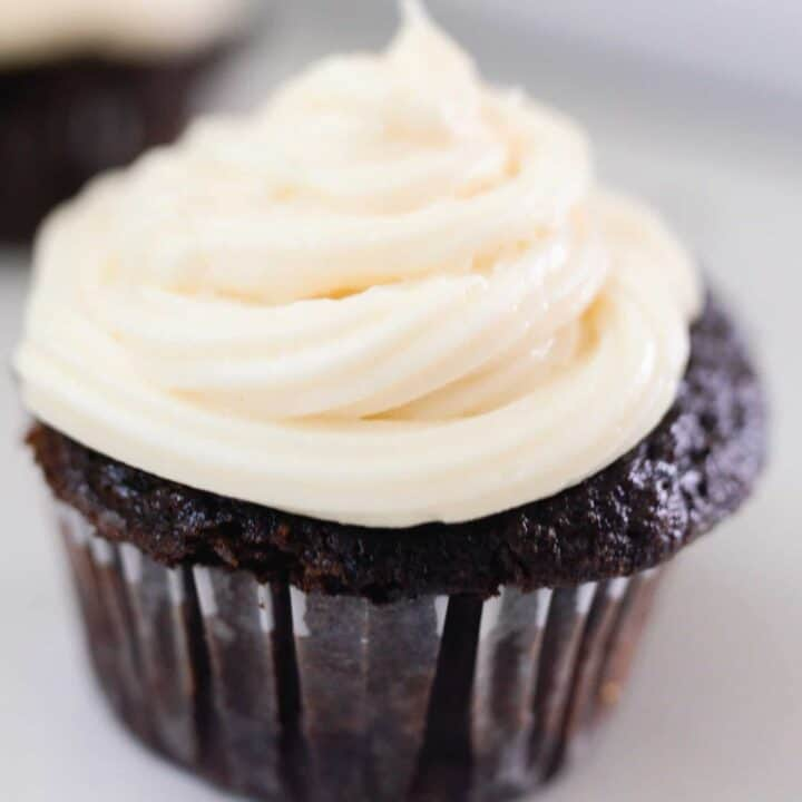 close up picture of a sourdough cupcake with white frosting on an white antique stove
