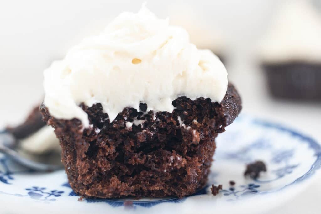 sourdough chocolate cupcake with white frosting cut in half on a white and blue antique plate