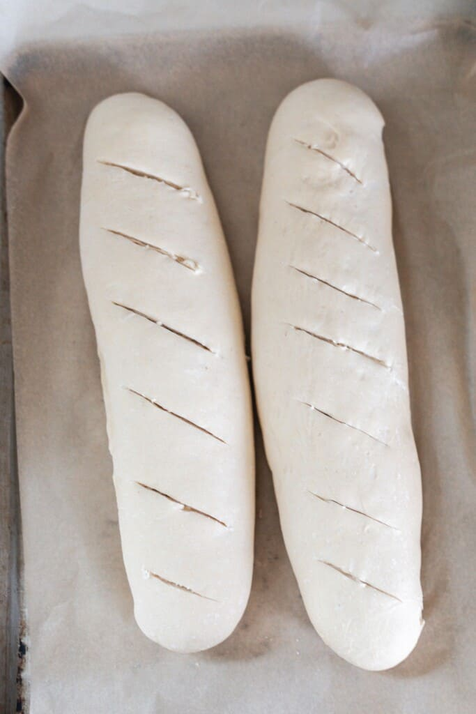 two raw sourdough baguettes slashed with a lame on top of a parchment lined baking sheet ready for the oven