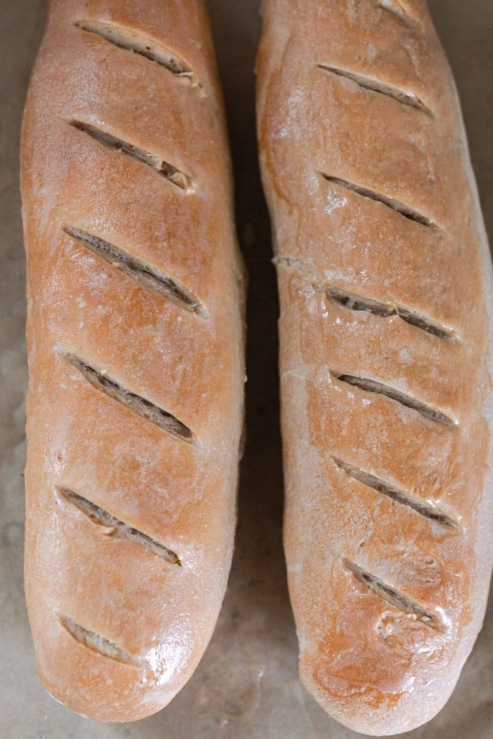 overhead photo of two baked sourdough French breads on parchment paper.