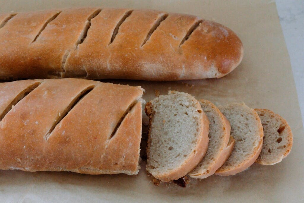 two loaves of sourdough French bread on parchment paper, on is sliced while the other is whole