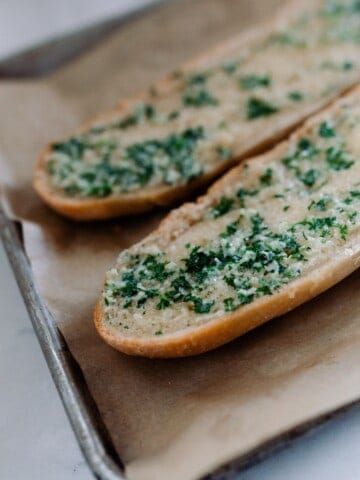 sourdough French bread cut in half and covered with garlic butter baked in the oven on parchment lined baking sheets
