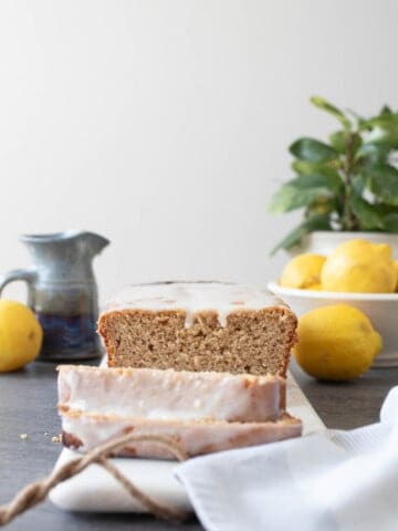 sourdough lemon pound cake with a lemon glaze sliced on a marble cutting board. A small gray pitcher, lemons, and a potted plant in the background