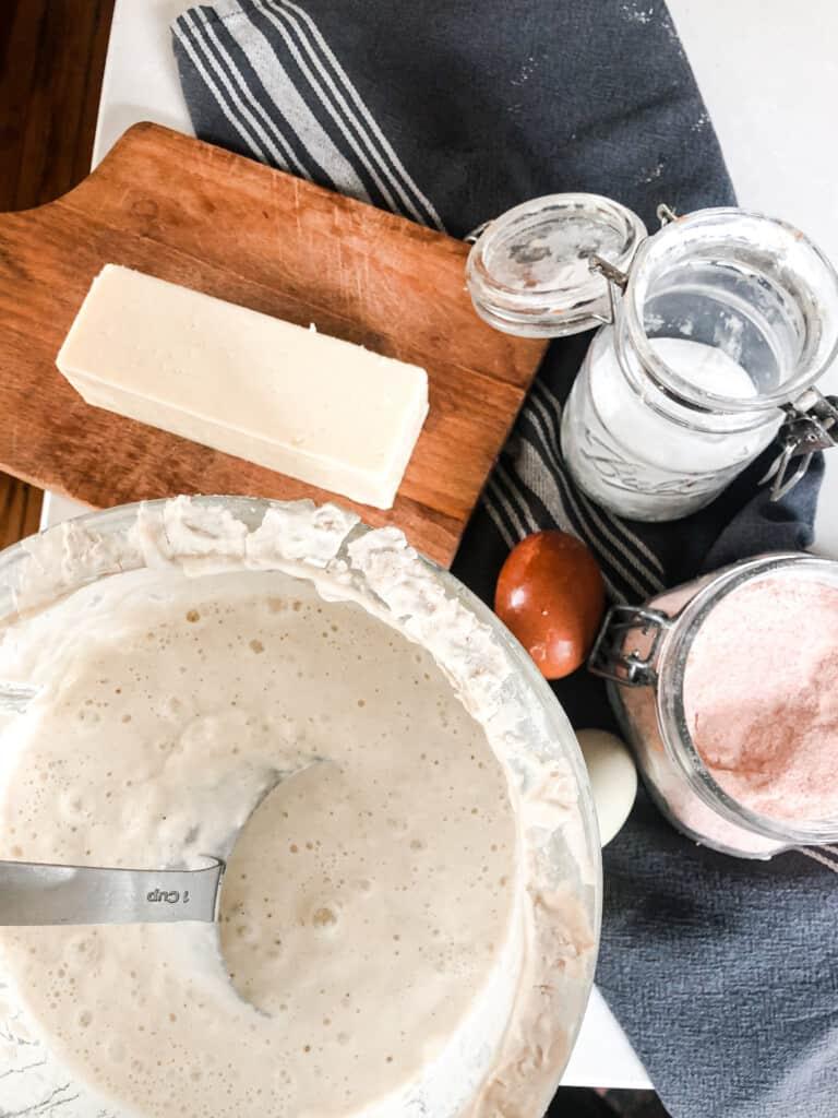 sourdough cheddar waffle ingredients: sourdough starter, salt, baking soda, cheese on a wood cutting board, and eggs