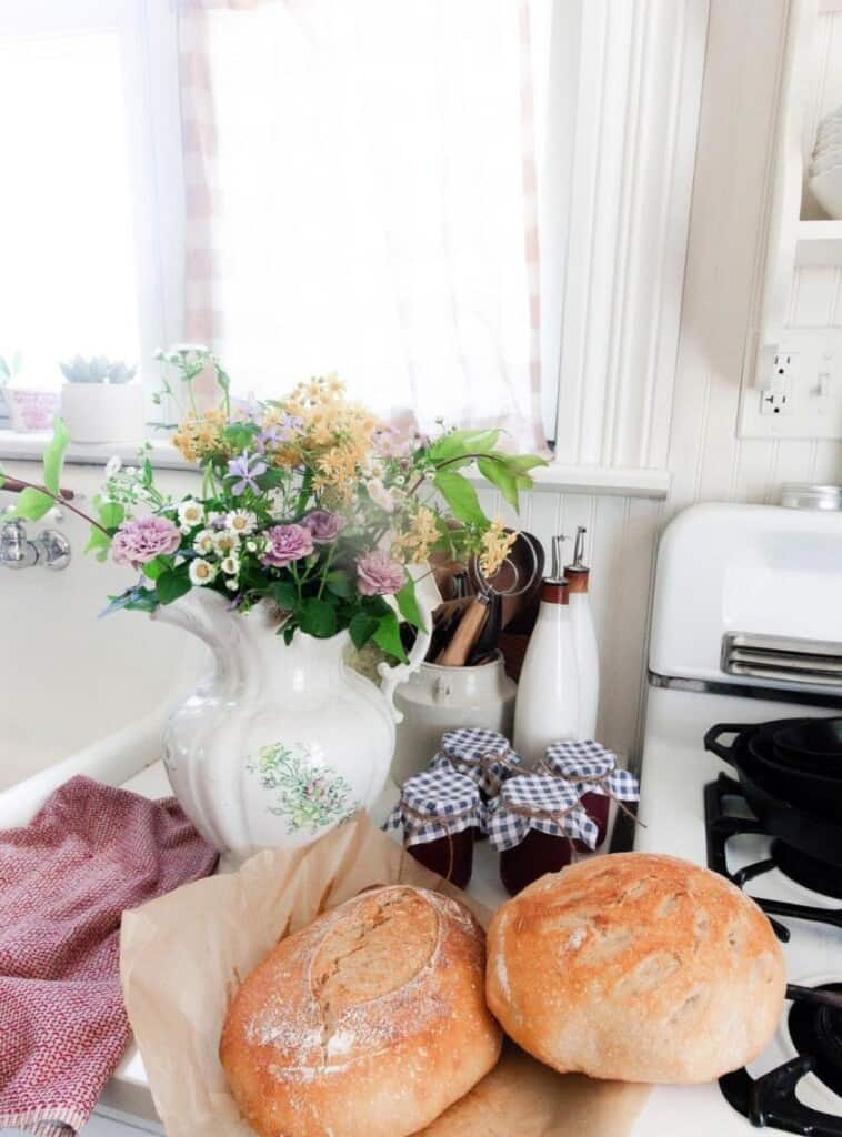 two loaves of homemade bread on parchment paper with a bouquet of flowers in an antique vase with two jars of jam to the right