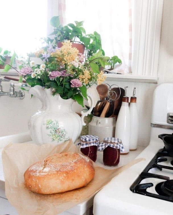 a loaf of homemade sourdough bread on parchment paper on a white countertop with two jars of jam and a bouquet of flowers in a vase in the background