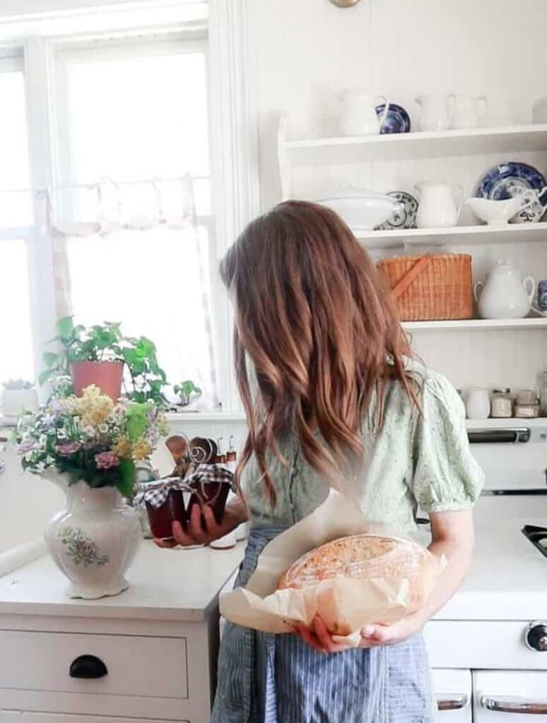 women holding a loaf of homemade bread in one hand and a couple jars of strawberry jam in the other hand in a white kitchen