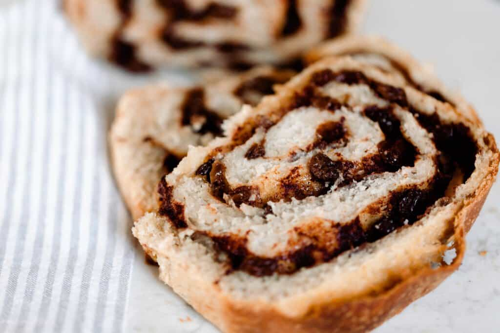 slices of swirled cinnamon raisin sourdough bread on a white and gray stripped tpwe;
