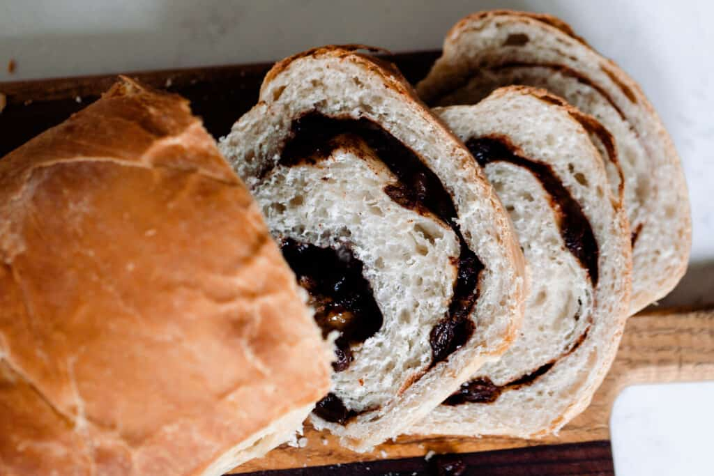 overhead photo of a loaf of sourdough raisin bread sliced on a wood cutting board on a white countertop