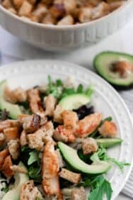 a white plate with a greens, avocados, and sourdough croutons with a bowl of croutons and a half of avocado in the background