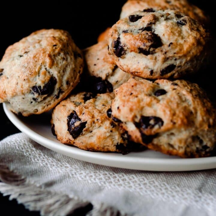 sourdough scones with chocolate chips and coconut stacked on a cream colored plate on a cream colored woven towel