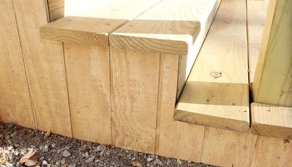 the side of wood steps covered with wood siding.
