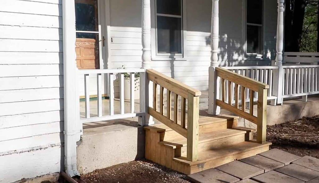 finished picture of front porch wood steps attached to a Victorian farmhouse front porch.
