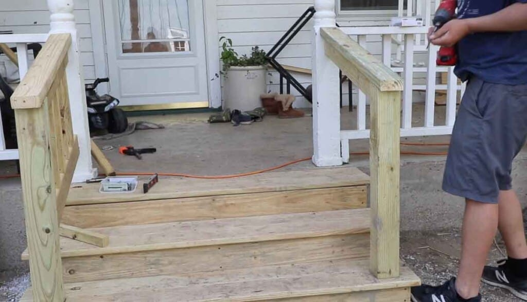 man adding a 2 by four to the top of a front porch step hand rail to finish it off.