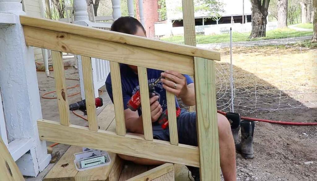man drilling spindles into a hand rail of front porch steps to match the spindles on the front porch.