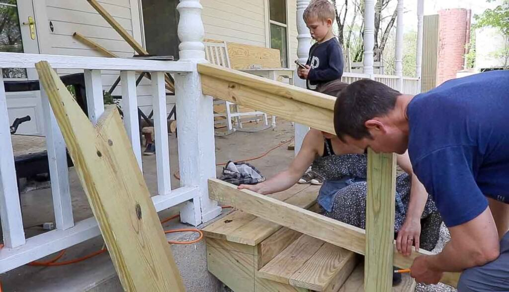 man and women adding a second bottom rail to a hand rail for support