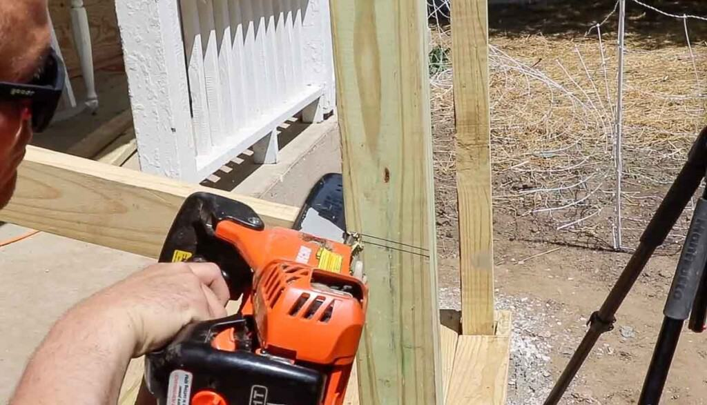 man using a chainsaw to cut off the top of a post to create a hand rail on front porch stairs