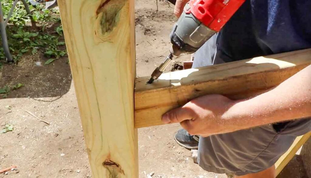 ma drilling in a 2x4 into a post to create a hand rail.
