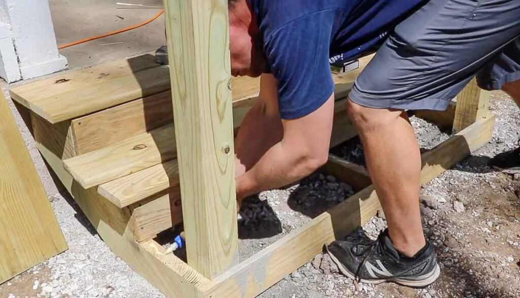 man adding wood glue to the top of stair stringers with a post