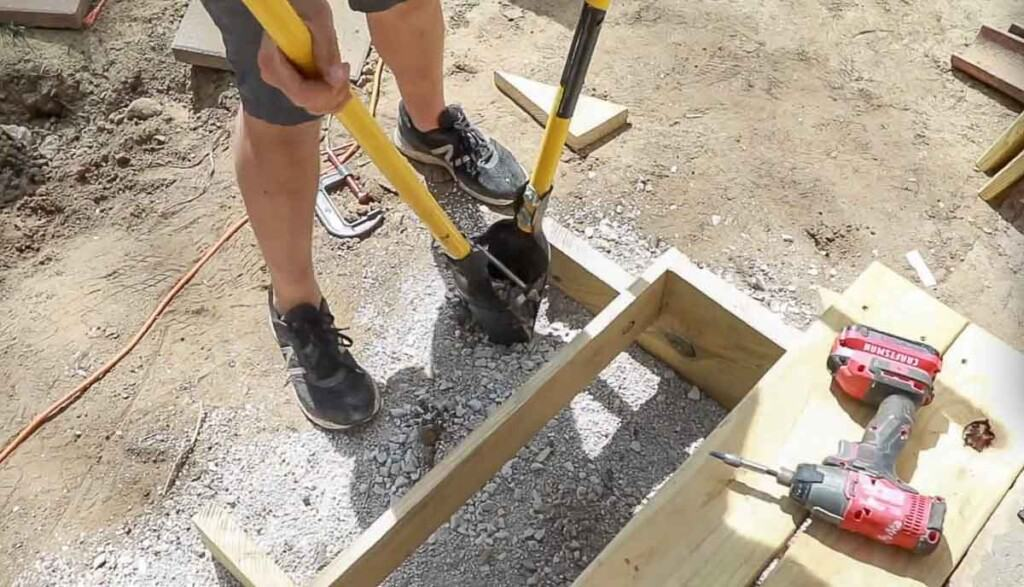 Man using a post hold digger to dig out a hole right next to stair stringers to add a post.