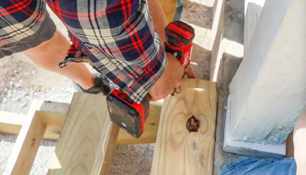Man drilling stair treads into a stair stringers on a front porch