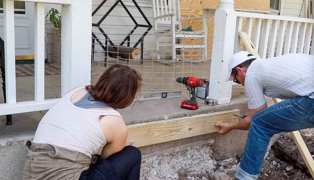 man and women drilling a wood board  to a concrete porch that will act as an an anchor for front steps.