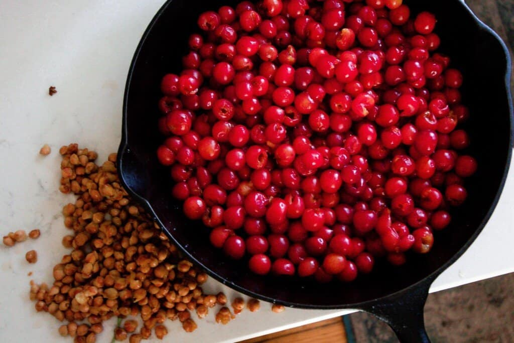 pitted cherries in a cast iron skillet ton a white quartz countertop