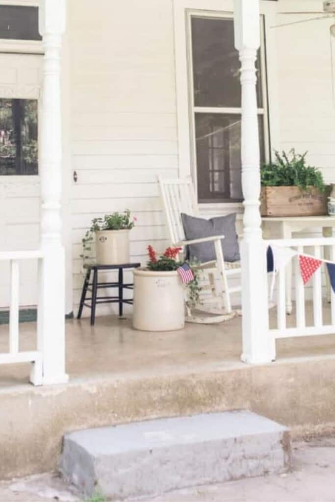 before picture of a a white victorian farmhouse front porch with a concrete step. Vintage pots with flowers and a rocking chair sit on a the porch