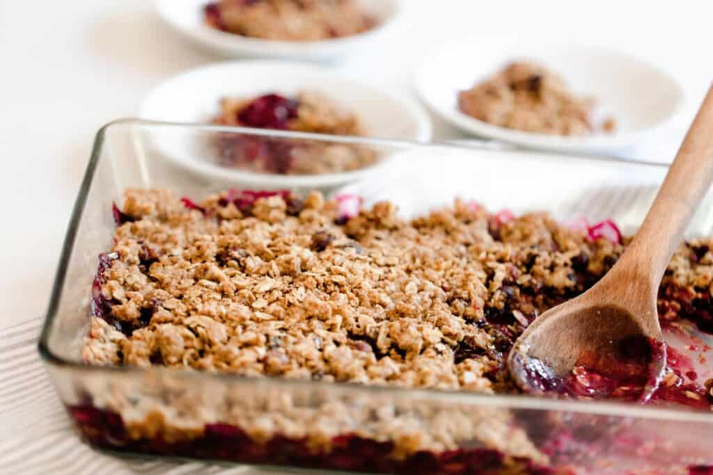 glass baking dish with einkorn berry crisp in it with a wooden spoon in the crisp. Plates of crisp are in the background