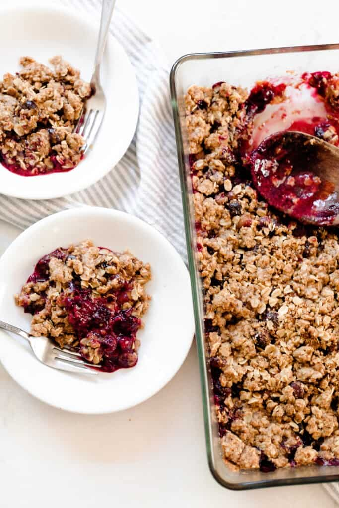a baking dish of einkorn berry crisp with two bowl os crisp to the left
