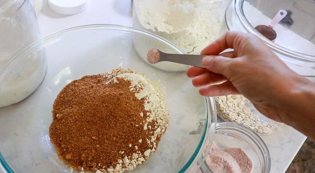 salt being added to a bowl of einkorn flour, coconut sugar, and oats in a glass bowl