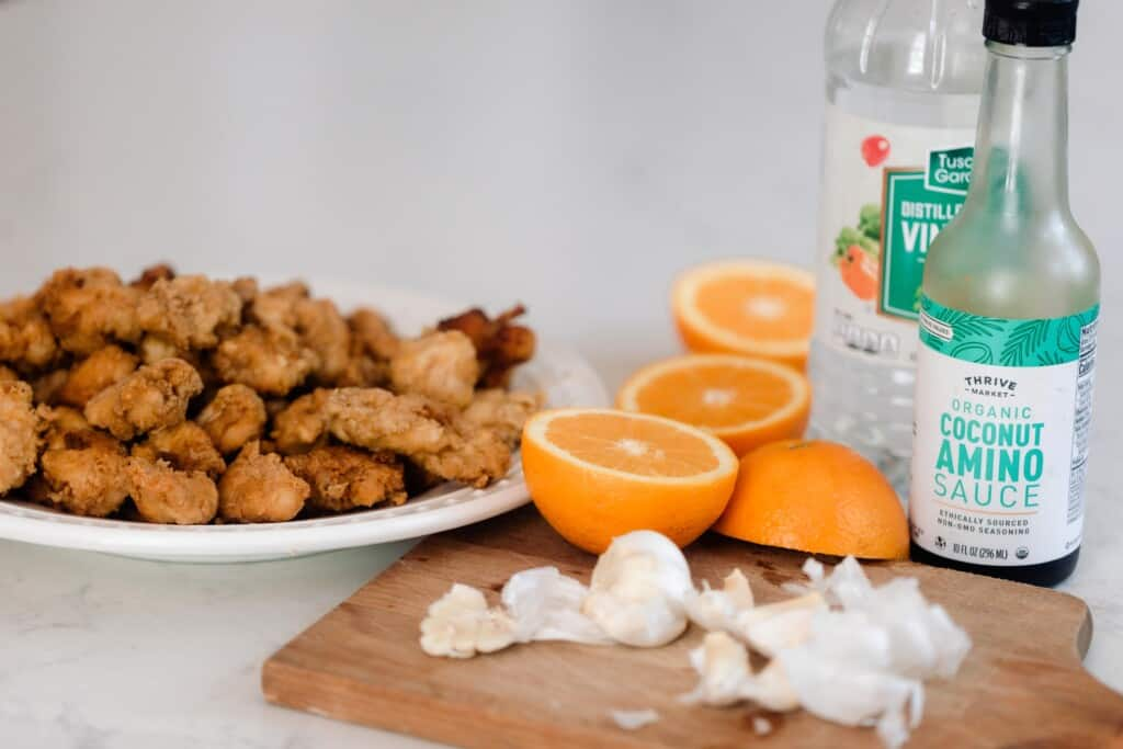 einkorn fried chicken on a white plate with oranges sliced in half, a cutting board with garlic on top. A bottle of coconut aminos and vinegar sit behind the cutting board.