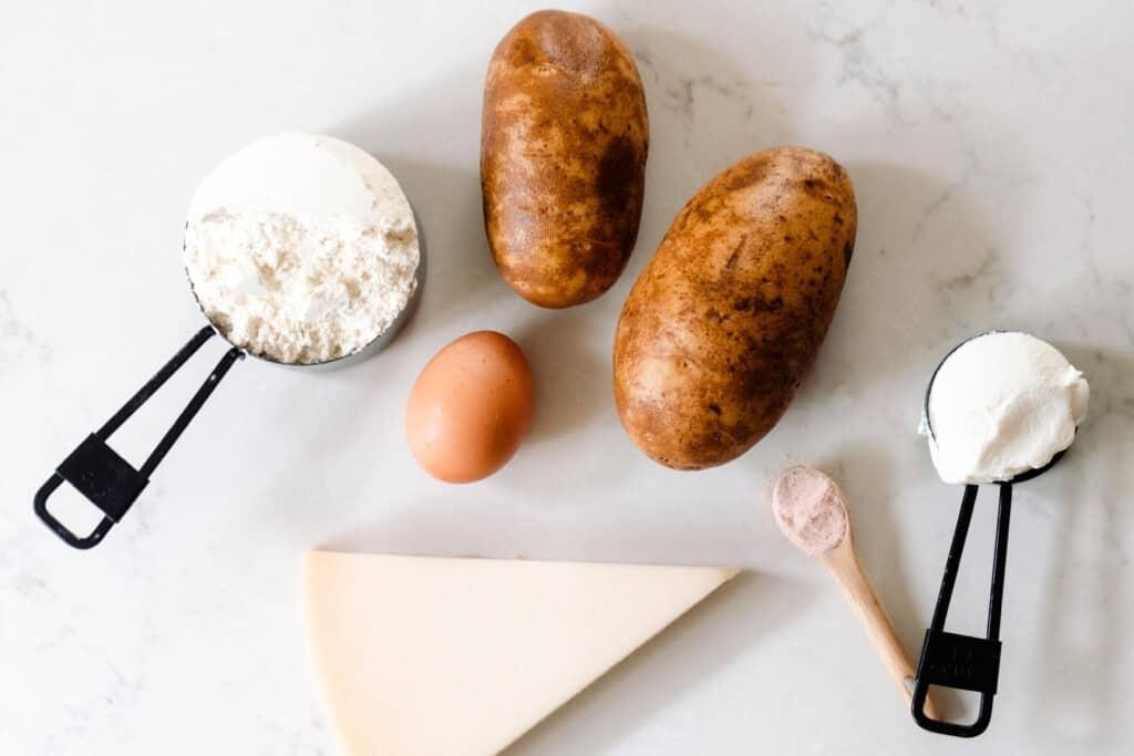 potato, einkorn flour, ricotta, egg, and a wedge of fresh parmesan cheese on a white quarts countertop