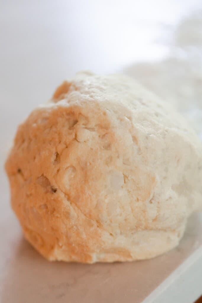 a ball of gnocchi dough on a white quarts countertop