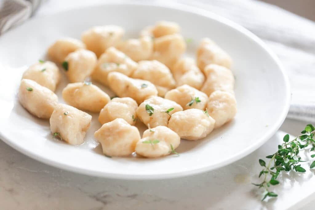 homemade einkorn gnocchi in a white bowl, topped with herbs, on a white quartz countertop with fresh thyme to the right