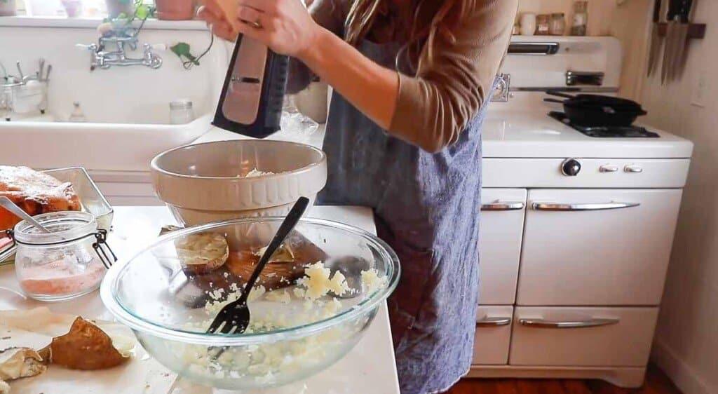 women wearing a blue pinafore apron grating fresh parmesan cheese into a bowl