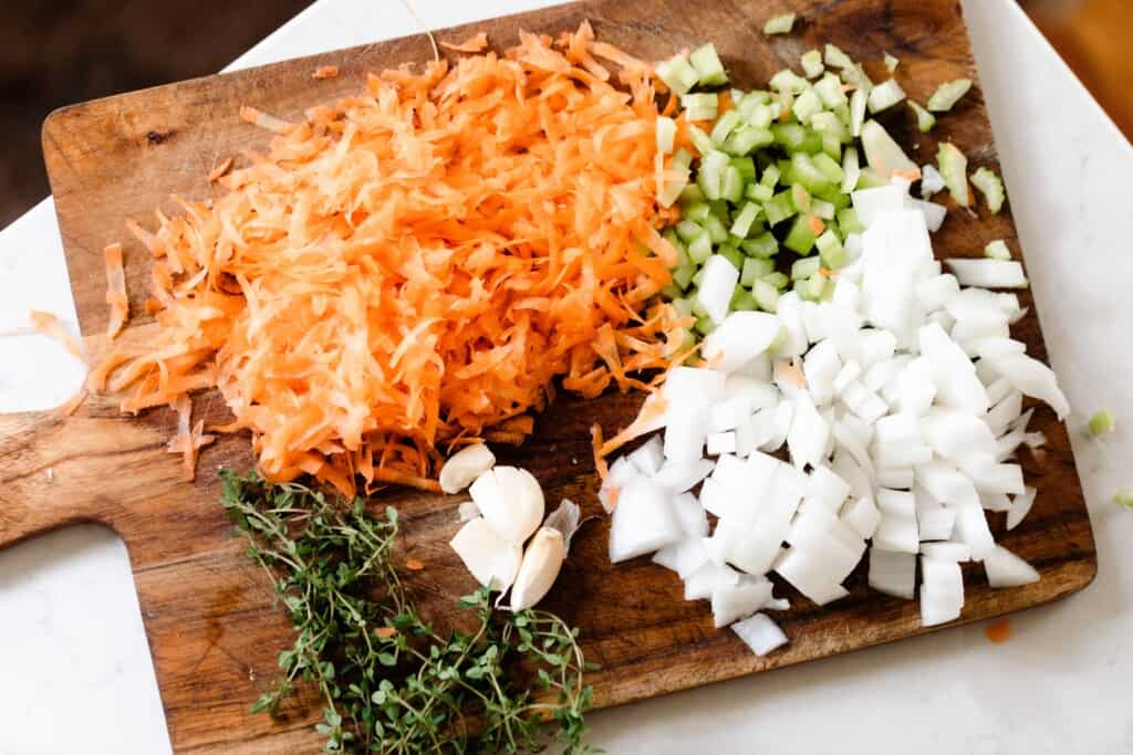 a cutting board filled with chopped onion, celery, carrots, whole garlic and fresh thyme